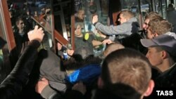 """Бирюлеводаги дарғазаб оломон """"Бирюза"""" савдо маркази ойнасини синдирмоқда, Москва, 2013 йилнинг 13 октябри."""