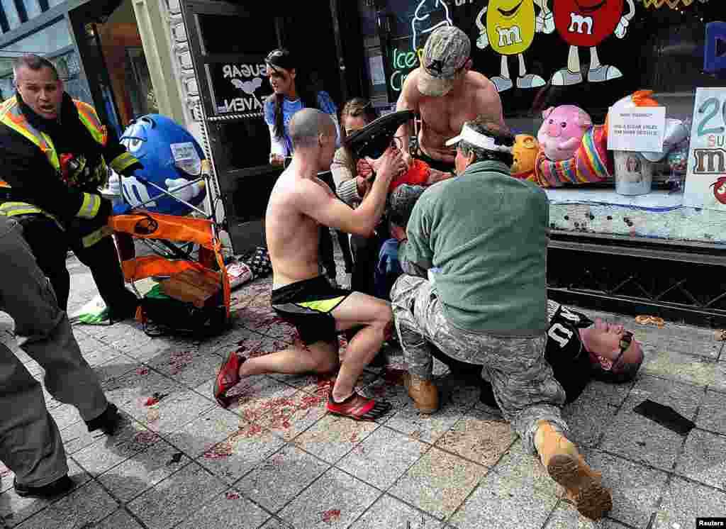 Bystanders tend to a man injured in the explosions.