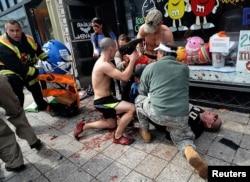 Прохожие оказывают первую медицинскую помощь мужчине, раненному из-за взрыва бомбы во время марафона. Бостон, 15 апреля 2013 года.