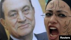 Девушка с портретом Хосни Мубарака у здания суда в Каире, где рассматривается дело бывшего президента Египта. Иллюстративное фото.