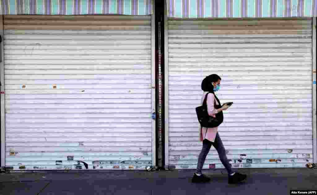 Иранская женщина в маске для защиты от COVID-19 проходит мимо закрытого ставнями магазина в центре Тегерана