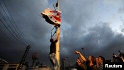Подъем сирийского и российского флагов в одном из городов Сирии