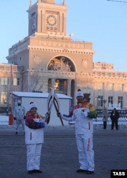 Эстафета олимпийского огня в Волгограде на фоне вокзала