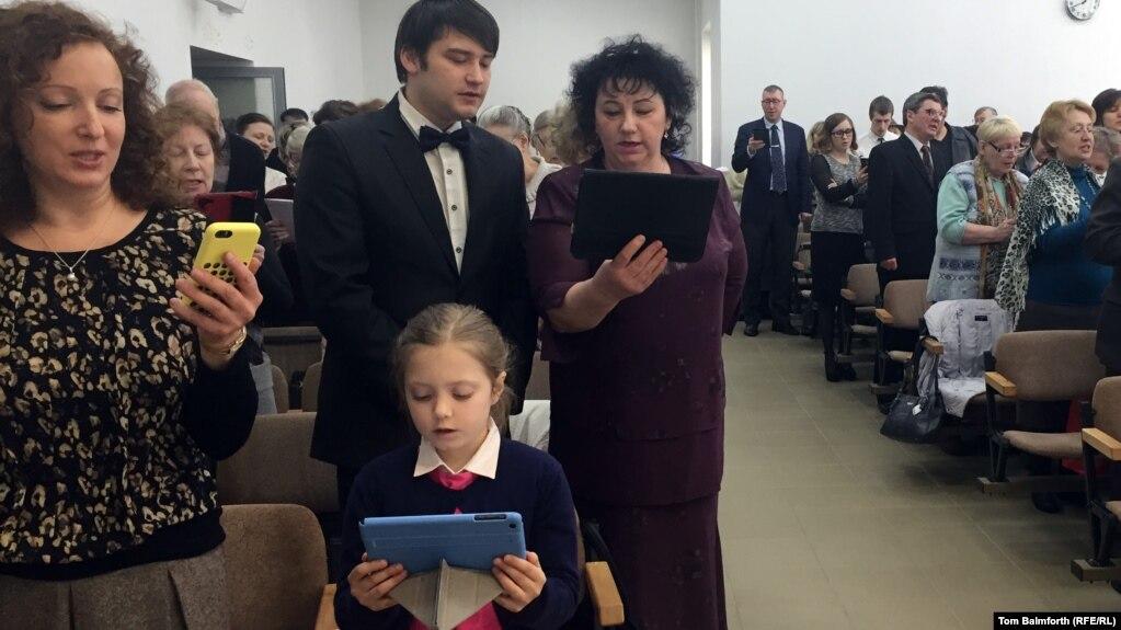 Adoradores muitas vezes lêem de smartphones e tablets, pois os envios de Bíblias foram interceptados na fronteira russa pelos costumes desde 2015.