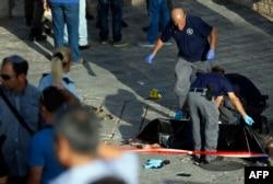 نیروی پلیس اسرائیل در حال پوشاندن جسد یکی از حملهکنندگان با چاقو هستند که هدف قرار گرفته است