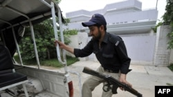 A Pakistani policeman climbs on a police vehicle in front of the locked residence of Pakistani-American Faisal Shahzad in Peshawar
