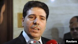 Syrian Prime Minister Wael al-Halqi says the government is not planning to surrender at talks in Geneva.