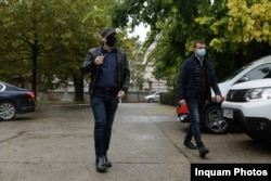 Florin Cîțu, cât pe ce să treacă neobservat de jurnaliști la intrarea în sediul PNL, camuflat cu șapcă și mască, într-o geacă de piele