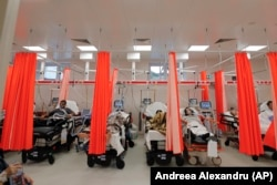 Patients lie on beds in an emergency room that has been turned into a COVID-19 unit due to the high number of cases, at the Bagdasar-Arseni hospital in Bucharest.