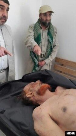 محمد باقرزاده، یکی از فرماندهان نیروی مسلح ایران، به جنازه منتسب به عزت ابراهیم الدوری اشاره میکند