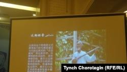 """Бээжин шаарында 2015-жылдын тогуздун айынын 19-20унда өткөрүлгөн """"Жуңгодогу уйгур дастандары боюнча эл аралык туңгуч илимий жыйындын"""" маалындагы баяндамадагы дастанчы Курбаннияз Курбандын сүрөтү."""