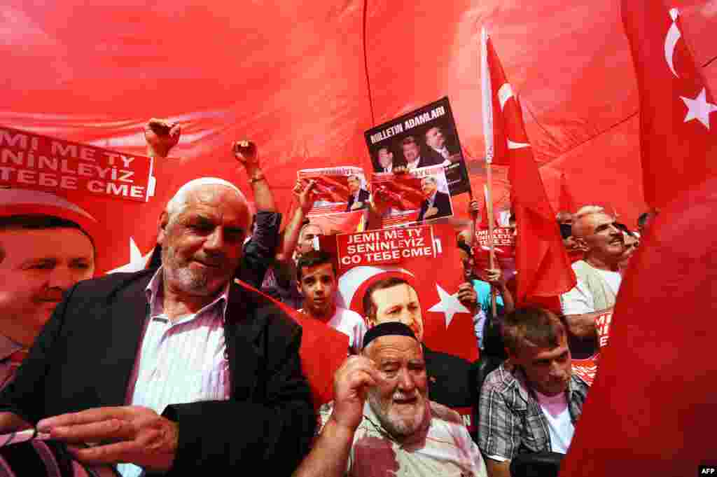 Members of the Turkish community in Macedonia hold Turkish national flags and posters of Turkish Prime Minister Recep Tayyip Erdogan during a rally in support of Erdogan in Skopje. (AFP/Robert Atanasovski)