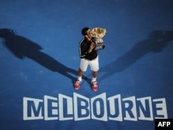 Novak Đoković ljubi trofej osvojen na turniru u Melburnu, 29. januar 2012.