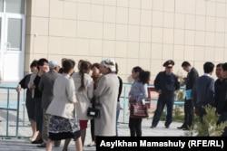Люди стоят возле здания, где проходит суд в Актау.