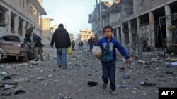 A Syrian boy runs while carrying bread following a reported airstrike by government forces in the town of Idlib, a major jihadist stronghold in northwestern Syria.