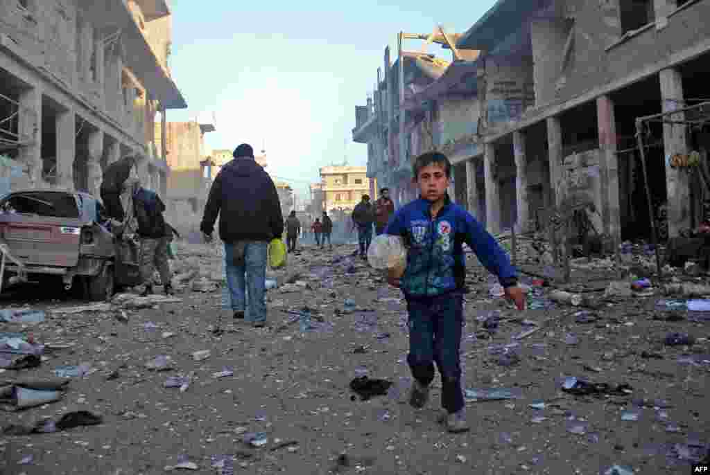 A Syrian boy runs while carrying bread following a reported air strike by government forces in the Syrian town of Binnish, on the outskirts of Idlib. (AFP/Omar Haj Kadour)