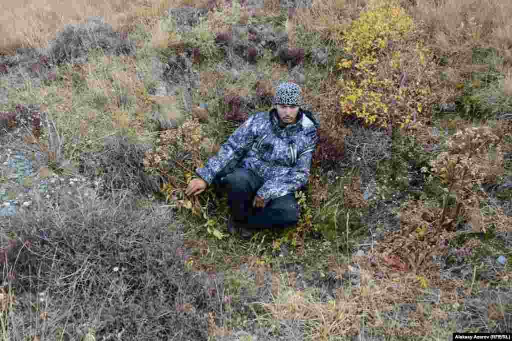 В этих же местах обнаружены и другие артефакты древности, кроме петроглифов – разграбленные курганы-захоронения, оградки для жилищ, древние тропы, ямы искусственного происхождения. Ученых это наводит на предположения, что здесь могло быть поселение охотников на древнем пути через горы. На этом фото Бекбол Нурмуханбетов сидит в яме искусственного происхождения глубиной чуть больше метра. Бекбол предположил, что это схрон древних охотников на горных козлов и других диких животных.