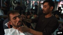 An Afghan barber cuts a customer's hair at a Kabul barbershop prior to the Taliban takeover.