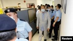 Apple Daily кеңсесінде тінту жүргізіп жатқан полиция қызметкерлері және медиамагнат Джимми Лай. Гонконг, 10 тамыз 2020 жыл.