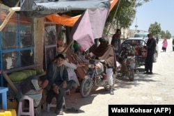 Taliban fighters stand along a road with their motorcycles at a local bazaar in the Andar district of Ghazni Province on June 3.