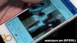 Հայաստան -- Ընտրական հանձնաժողովի անդամը ցույց է տալիս կրկնաքվեարկության տեսանկարահանումը իր հեռախոսով, Երևան, 6-ը դեկտեմբերի, 2015թ․