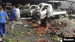 Banorët lokalë në Irak e inspektojnë një vend ku më herët kishte shpërthyer një bombë