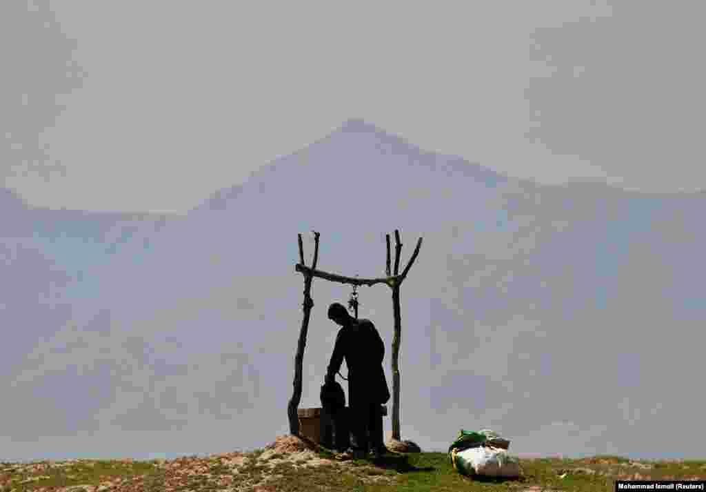 Кабул маңындағы елдімекендердің бірінде құдықтан су алып жатқан ауған баласы.