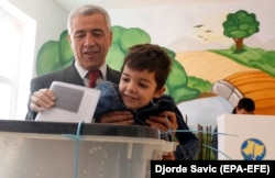 Oliver Ivanovic casts his vote in local elections along with his son at a polling station in northern Mitrovica in October.