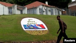 A man walks past a floral display announcing the 5th BRICS summit in Durban, South Africa.