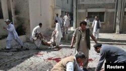Men remove dead bodies from the site of the suicide bomb attack inside a civil hospital in Quetta on April 16.
