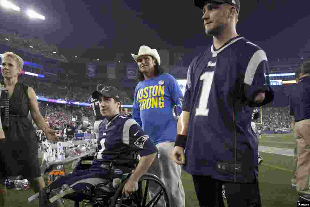 Boston marathon bombing victim Jeff Bauman (left), responder Carlos Arredondo (center), and Taylor Morris (right) of the U.S. Navy are honored in a ceremony before the New York Jets face the New England Patriots in a football game in Foxborough, Massachusetts, on September 12, 2013.