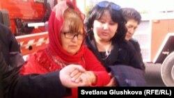Бағжан Аязбекованың (ортада) жеті күн кран басында өткізген наразылық шарасынан соң жерге түскен кезі. Астана, 4 маусым 2013 жыл.