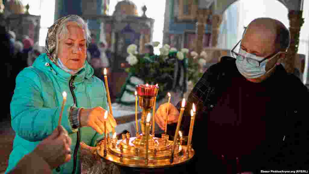 Прихожане молятся и ставят свечи за здравие и за упокой