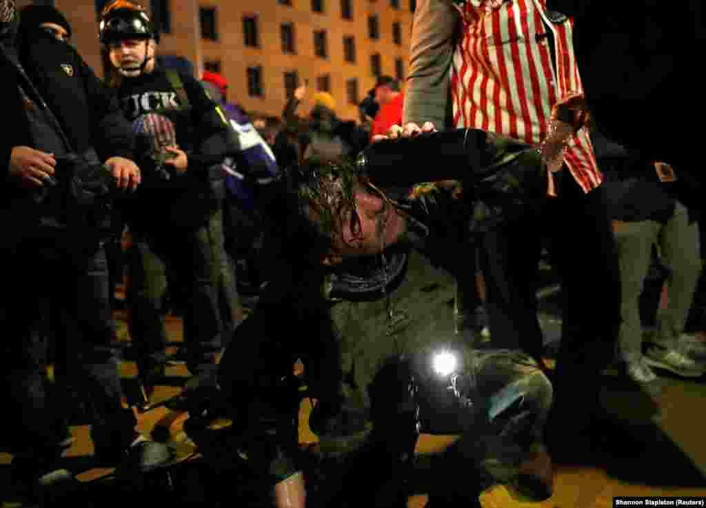 Прихильник президента США Дональда Трампа миє очі після того, як поліція застосувала сльозогінний газ під час протестів у Вашингтоні, США, 5 січня 2021 року