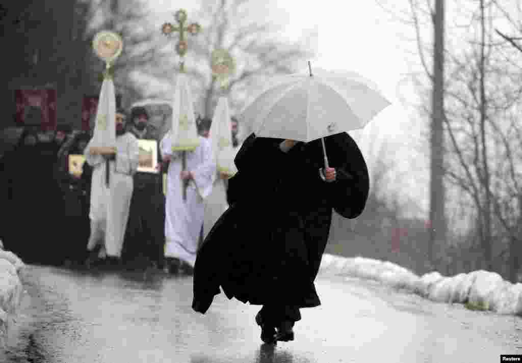 A Macedonian priest, carrying an umbrella, heads a procession during an Epiphany celebration in the village of Bitushe about 150 kilometers west of Skopje. (Reuters/Ognen Teolovski)