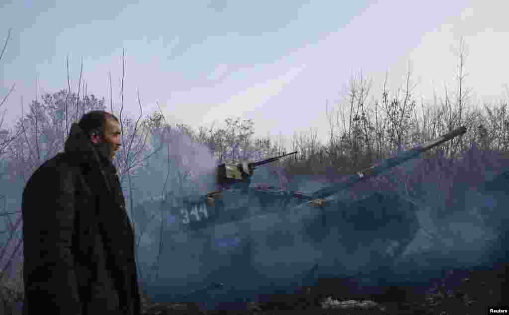 A man stands next to a pro-Russian separatist tank near the village of Rozsypne in eastern Ukraine. (Reuters/Maxim Shemetov)