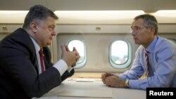 Ілюстративне фото. Президент України Петро Порошенко (л) і генеральний секретар НАТО Єнс Столтенберґ розмовляють в літаку, Львів, 21 вересня 2015 року