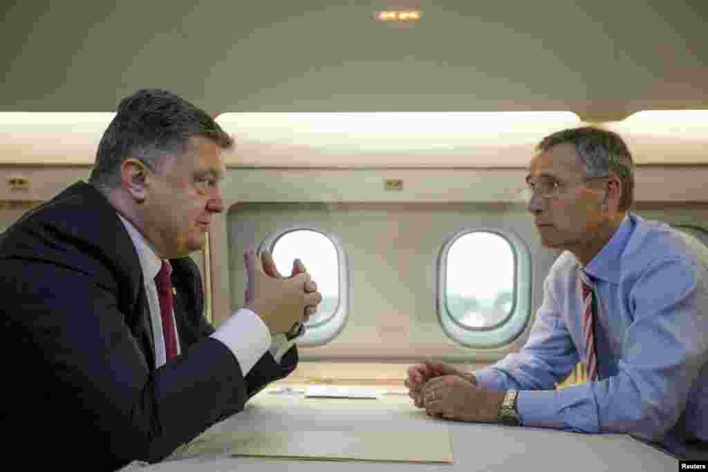 Президент України Петро Порошенко (ліворуч) та генеральний секретар НАТО Єнс Столтенберґ спілкуються у салоні літака у Львові. 21 вересня 2015 року