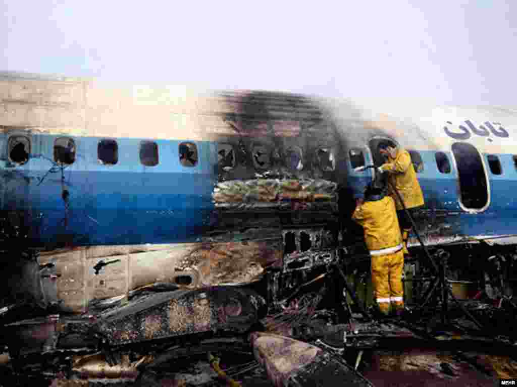 Workers inspect a plane that crash-landed at Mashhad Airport in northeastern Iran on January 24. - At least 46 people were injured when the Taban Air plane caught fire shortly before landing. Photo by MEHR