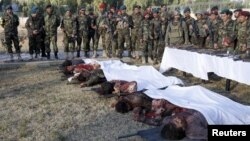 Afghan security forces stand next to the bodies of some of the Taliban insurgents killed by Afghan security forces after the Taliban attacked Kandahar Airfield.