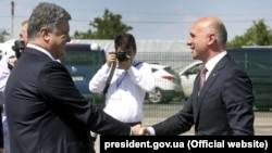 Moldovan Prime Minister Pavel Filip (right) and Ukrainian President Petro Poroshenko shake hands at the official opening of a joint border checkpoint at Kuchurgan-Pervomaisk.