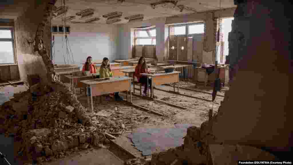 One photo shows girls sitting in a classroom destroyed by fighting.