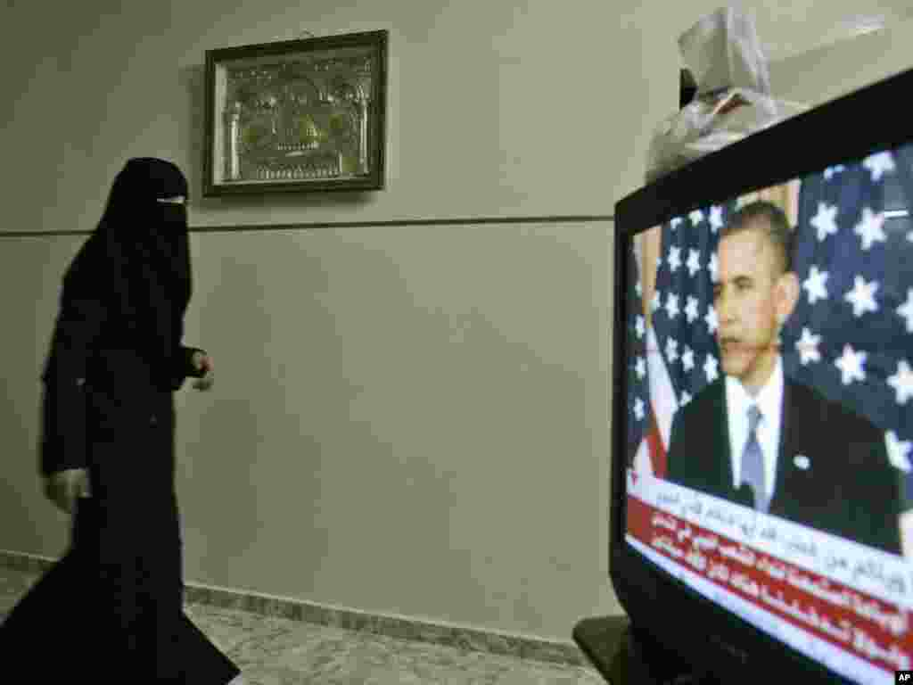 A veiled Palestinian woman walks near a television during a major Mideast foreign policy speech by U.S. President Barack Obama, in the West Bank city of Nablus.Nasser Ishtayeh for The AP
