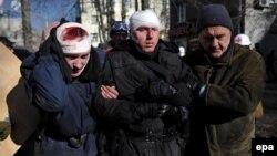 Двое раненых полицейских идут к машинам скорой помощи в Киеве 18 февраля 2014 года.