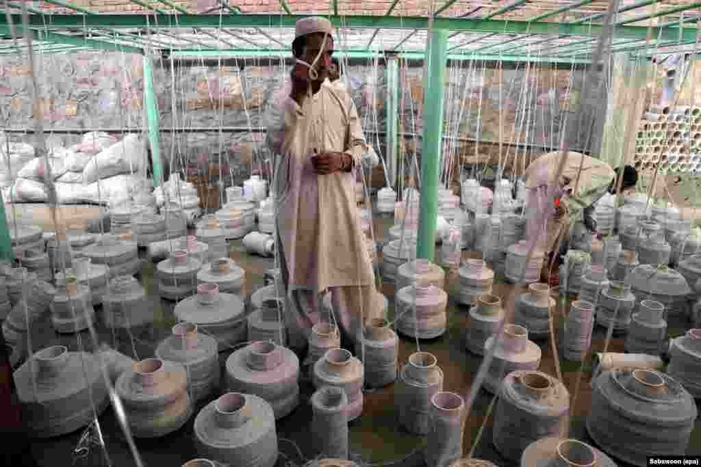 A worker stands among drums of spun fiber