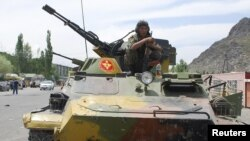 Kyrgyzstan -- A Kyrgyz serviceman sits on an armoured vehicle in the city of Osh, southern Kyrgyzstan, 15Jun2010