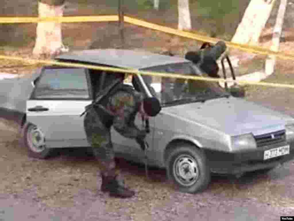 Полицейлер шабуыл болған жерде тұрған автокөлікті тексеріп жүр. Тараз, 12 қараша 2011 жыл.