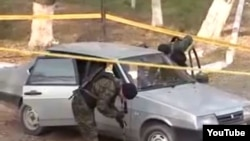 Police examine a car at the site of an attack in Taraz on November 12.