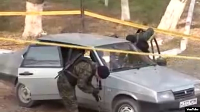 Police investigators examine a car at the site of the suicide attack in Taraz.