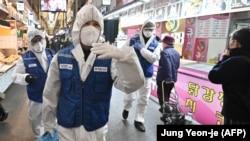 پرسنل بهداشتی در حال ضدعفونی بازارچهای در سئول